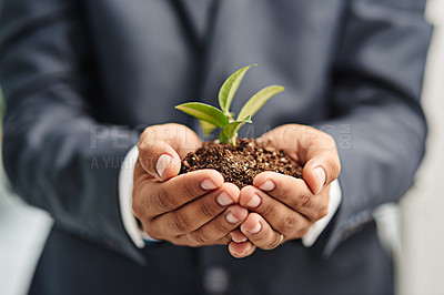 Buy stock photo Closeup shot of an unrecognizable businessman holding a sprouting plant in soil in his cupped hands