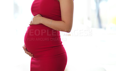 Buy stock photo Cropped shot of an unrecognizable pregnant young woman holding her belly while standing in her home