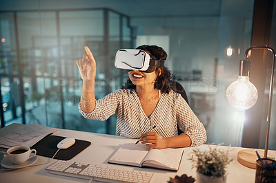 Buy stock photo Shot of a young businesswoman wearing a virtual headset and using a digital interface while working late in her office
