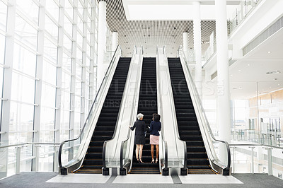 Buy stock photo Rearview shot of two unrecognizable businesswomen going up an escalator in the workplace