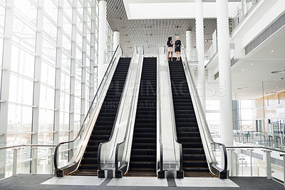 Buy stock photo Full length shot of two businesswomen having a discussion while coming down an escalator in the workplace