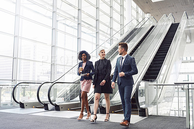 Buy stock photo Full length shot of a diverse group of businesspeople having a discussion while walking through a modern workplace