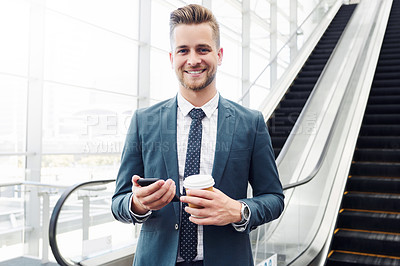 Buy stock photo Cropped portrait of a handsome young businessman using a smartphone while standing alone in the workplace