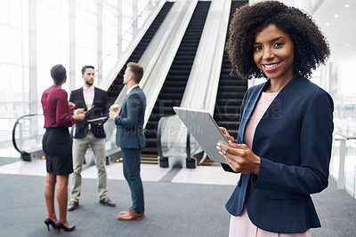 Buy stock photo Cropped portrait of an attractive young businesswoman using a digital tablet in an office with her colleagues standing in the background