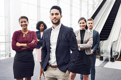 Buy stock photo Cropped portrait of a handsome young businessman standing with his colleagues in a modern workplace
