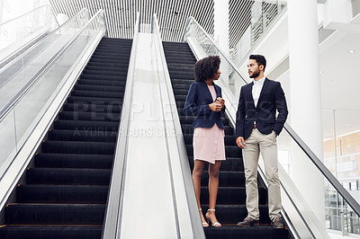 Buy stock photo Full length shot of two young businesspeople having a discussion while coming down an escalator in a modern workplace