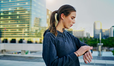 Buy stock photo Shot of a young woman looking at her watch while exercising in the city