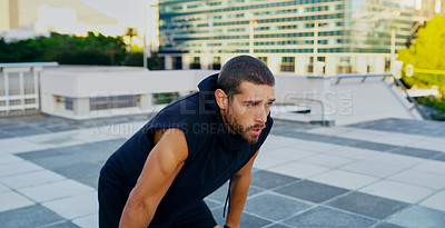 Buy stock photo Shot of a young man taking a break from his workout in the city