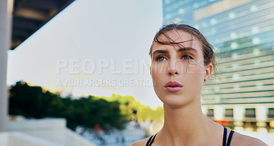 Buy stock photo Shot of a young woman taking a break from her workout in the city