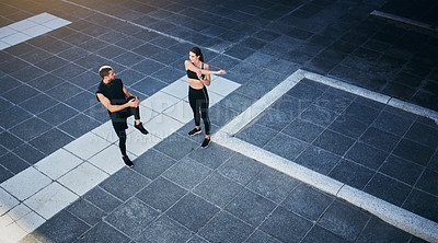 Buy stock photo Shot of a young couple stretching during their workout in the city