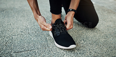 Buy stock photo Cropped shot of a man tying his shoelaces during a workout in the city