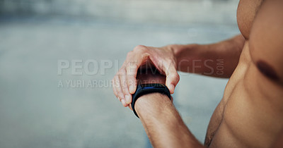 Buy stock photo Cropped shot of an unrecognizable shirtless man looking at his watch while exercising in the city