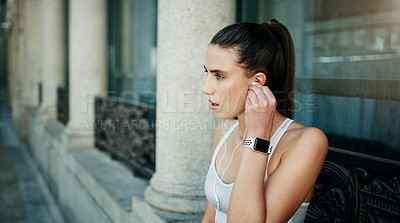 Buy stock photo Shot of a young woman listening to music during her workout in the city