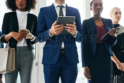Buy stock photo Cropped shot of a diverse group of businesspeople standing and using technology while waiting for their interview in the office