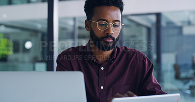 Buy stock photo Shot of a handsome young businessman using a digital tablet and laptop in her office