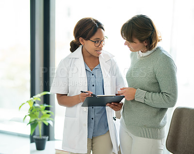Buy stock photo Shot of a young doctor writing down notes on a clipboard during a consultation with a patient inside her office