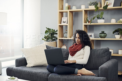Buy stock photo Full length shot of an attractive young woman using a laptop while relaxing on her couch at home