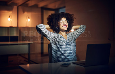 Buy stock photo Shot of a beautiful young businesswoman relaxing with her hands behind her head while working late shift in her office
