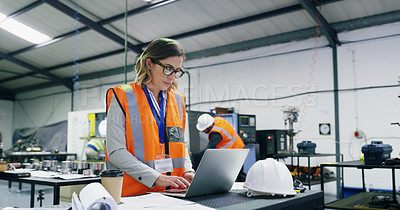 Buy stock photo Shot of a young engineer using a laptop in an industrial place of work