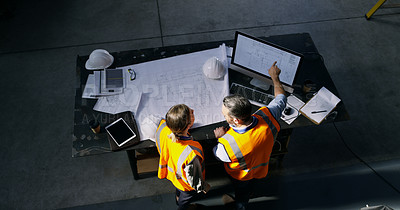 Buy stock photo Shot of two engineers using a computer while going over a blueprint in an industrial place of work