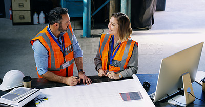Buy stock photo Shot of two engineers going over a blueprint together in an industrial place of work