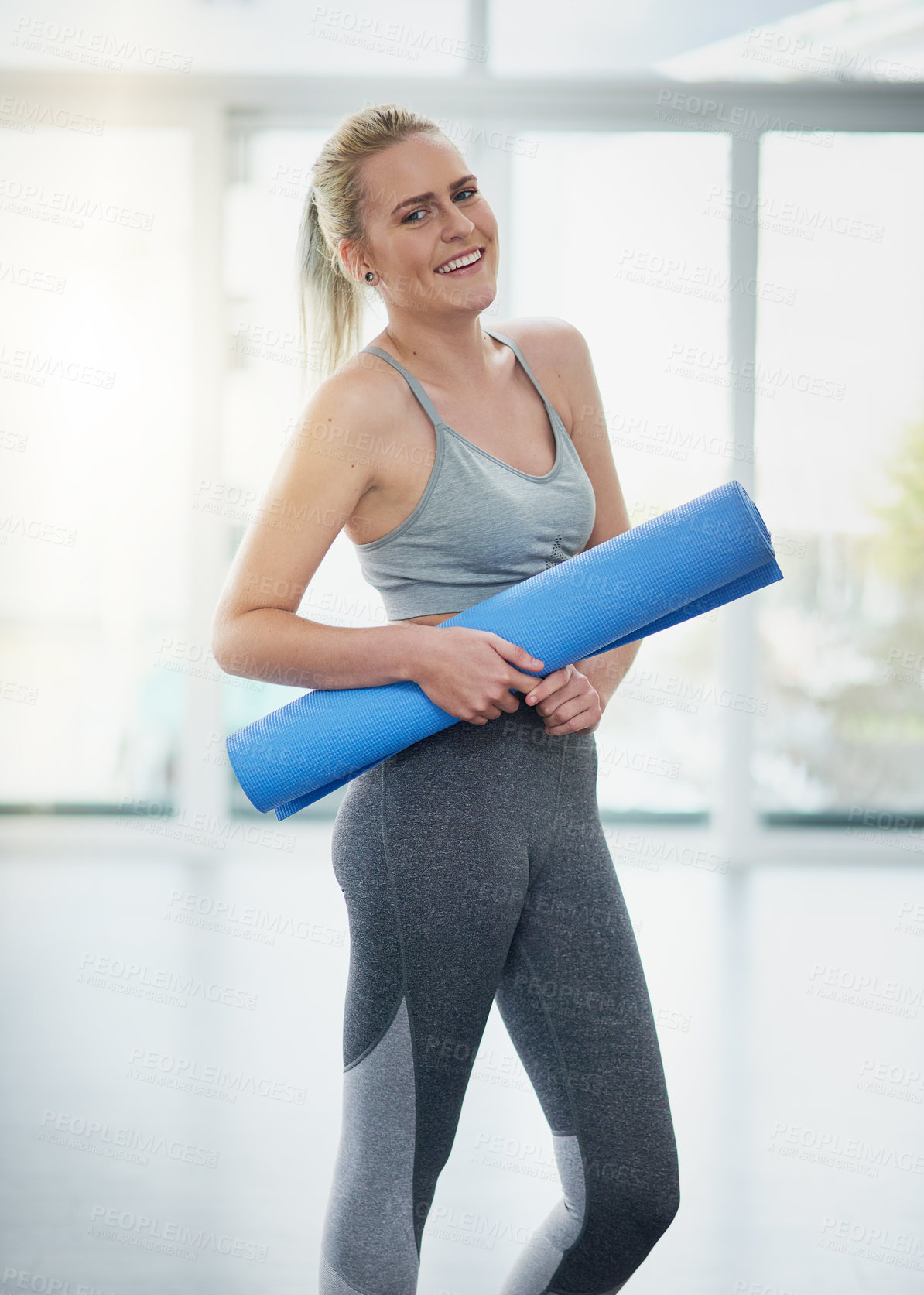 Buy stock photo Portrait of a sporty young woman holding a yoga mat in a studio