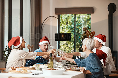 Buy stock photo Cropped shot of a cheerful family having a celebratory toast while having lunch during Christmas time