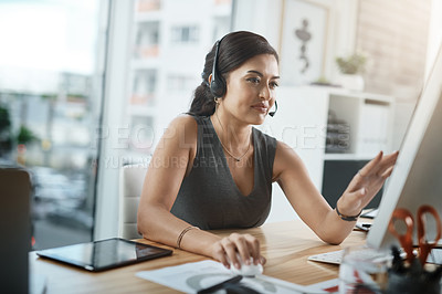 Buy stock photo Shot of a young businesswoman wearing a headset while working on a computer in an office