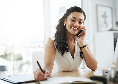 Buy stock photo Shot of a young businesswoman writing in a notebook and using a smartphone in a modern office