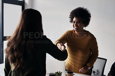 Buy stock photo Cropped shot of two young businesswomen greeting each other with a handshake before sitting down in the office