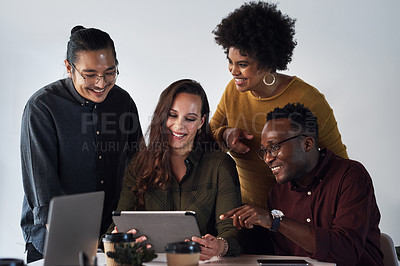 Buy stock photo Cropped shot of a diverse group of businesspeople working on a tablet together in the office