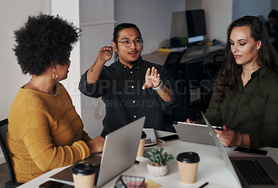 Buy stock photo Cropped shot of a diverse group of businesspeople sitting and having a meeting while using technology in the office