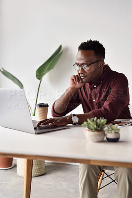 Buy stock photo Cropped shot of a handsome young businessman sitting alone and working on his laptop in the office