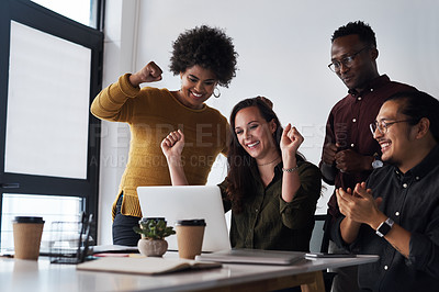 Buy stock photo Cropped shot of a diverse group of businesspeople celebrating together while looking at a laptop in the office