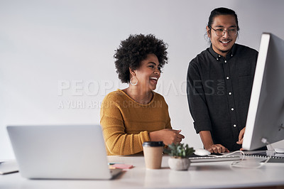 Buy stock photo Cropped shot of a two young coworkers working on a computer together in the office