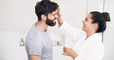 Buy stock photo Shot of a happy young woman applying moisturiser on her husband's face during their morning grooming routine at home