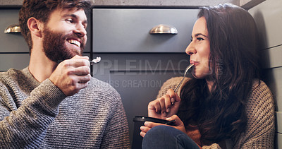 Buy stock photo Shot of a happy young couple sharing a tub of ice cream in their kitchen at home