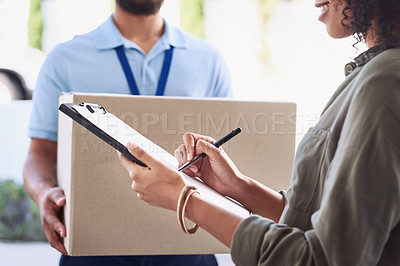 Buy stock photo Closeup shot of a woman signing for her delivery from the courier