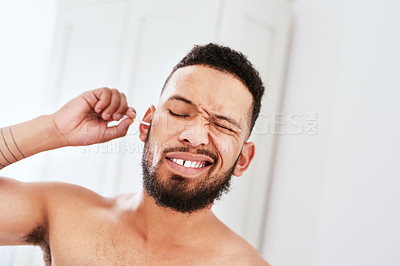 Buy stock photo Cropped shot of a handsome young man cleaning his ear with an earbud in his bathroom at home