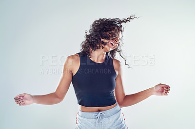 Buy stock photo Cropped shot of an attractive young woman flipping her hair and dancing against a gray background in the studio