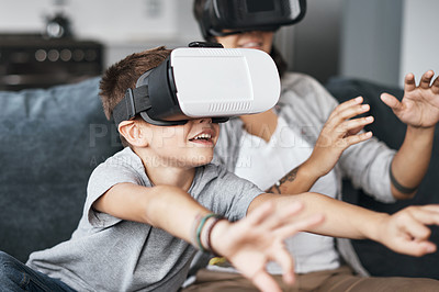 Buy stock photo Shot of a mother and her little son wearing VR headsets at home