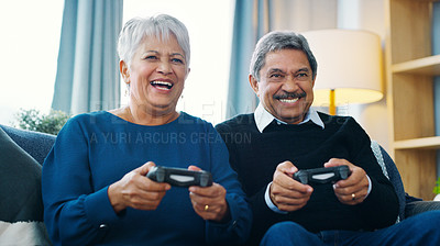 Buy stock photo Cropped shot of a cheerful elderly couple playing video games together while being seated on a sofa at home during the day