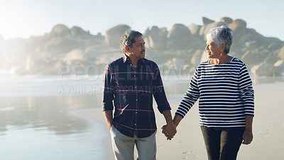Buy stock photo Cropped shot of an affectionate senior couple looking at each other while holding hands and walking along the beach together