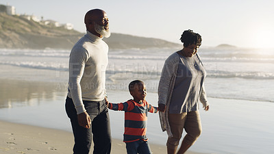 Buy stock photo Cropped shot of a happy senior couple holding their cute grandson's hands as they walk along the beach together