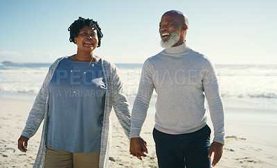 Buy stock photo Cropped shot of an affectionate senior couple smiling and holding hands as they walk along the beach together