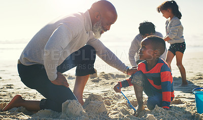 Buy stock photo Full length shot of a happy senior man bonding with his cute grandson as they play on the beach