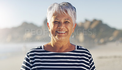 Buy stock photo Cropped portrait of an attractive senior woman standing alone  and smiling while enjoying a day out on the beach