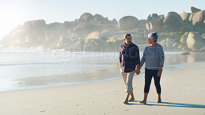 Buy stock photo Full length shot of an affectionate senior couple looking at each other while holding hands and walking along the beach together