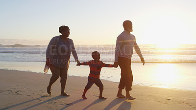 Buy stock photo Full length shot of a happy senior couple holding their cute grandson's hand as they walk along the beach together