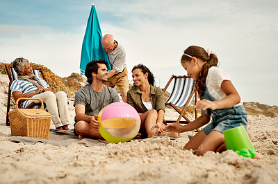 Buy stock photo Full length shot of an extended family spending the day together at the beach